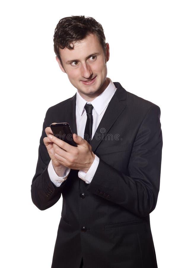 Twitters dell'uomo d'affari con uno smartphone immagine stock libera da diritti