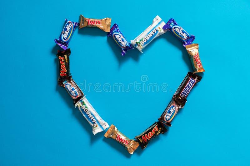 Twix, Milchstraße, kichert, Prämie, Mars-populäre Minisüßigkeits-Schokoriegel auf blauem Hintergrund in der Herzform Zu küssen Ma lizenzfreie stockbilder