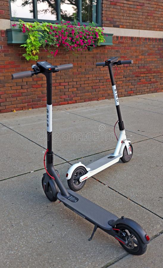 Two abandoned discharged `Bird` scooters on a sidewalk in downtown Cleveland, Ohio, USA. stock photos