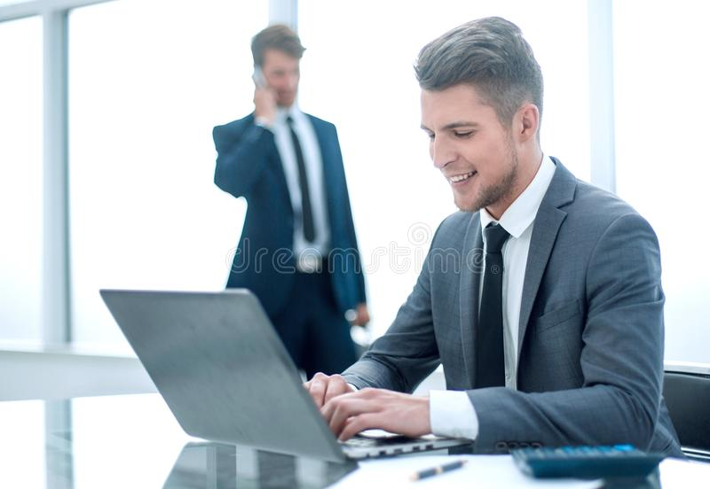Two accountants solve important issues. Two accountants solve important questions. One uses a laptop, the second is talking on the phone royalty free stock photography
