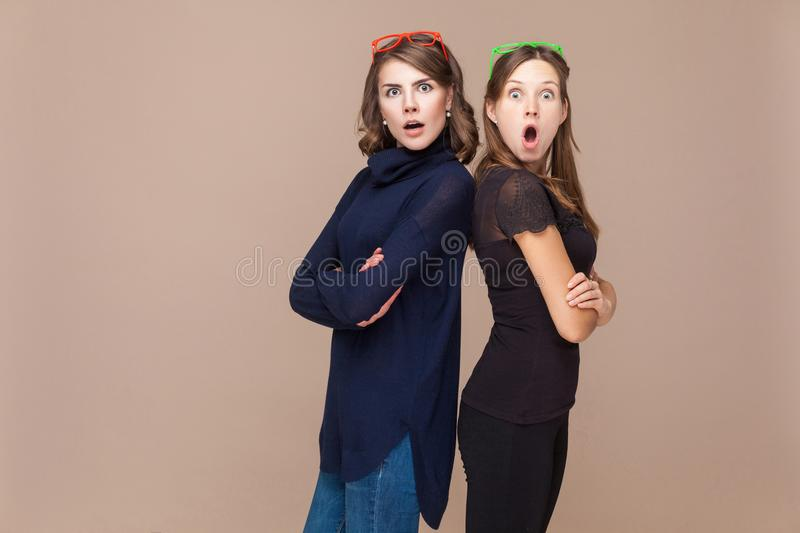 Two acquaintances standing back to back and looking at camera wi. Th shocked face. Studio shot stock photos
