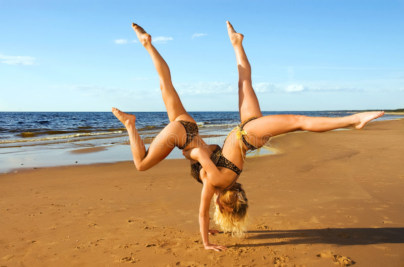 Two acrobatic girl on the beach. At the sea royalty free stock photo