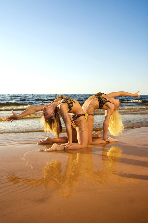 Two acrobatic girl on the beach. (reflected in water stock photos