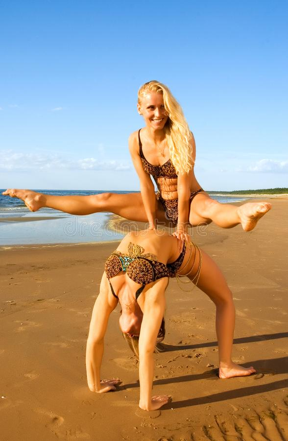 Two acrobatic girl on the beach royalty free stock images