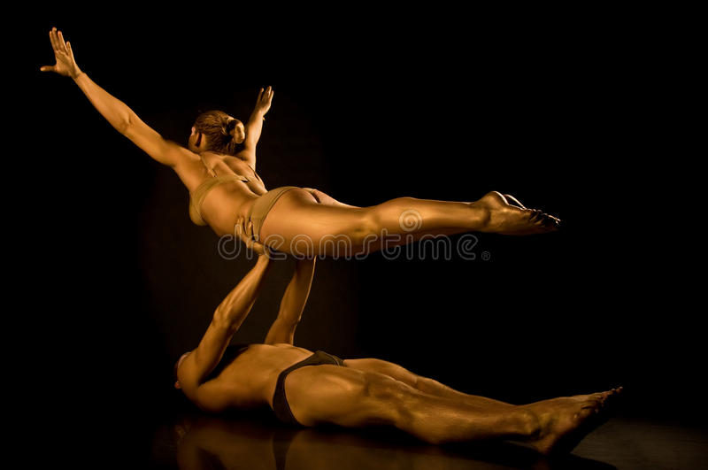 Two acrobats toned in gold. Making tricks royalty free stock image