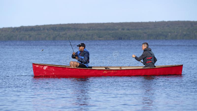 Casting for Small Mouth Bass from a Red Canoe on Georgian Bay. Two active fishermen on Georgian Bay near Christian Island cast a line from a red kevlar canoe stock images