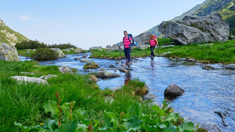 Two active, fit women hikers crossing a mountain river by stepping on rocks, with heavy camping backpacks and trekking poles. royalty free stock image