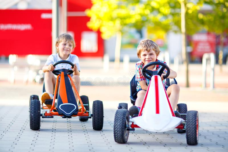 Two active little kid boys driving pedal race car in summer garden, outdoors. Children, best friends racing with fast royalty free stock photo