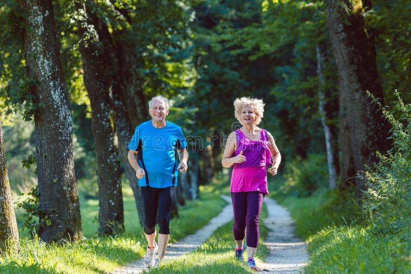 Two active seniors with a healthy lifestyle smiling while joggin. Full length front view of two active seniors with a healthy lifestyle smiling while jogging stock photos