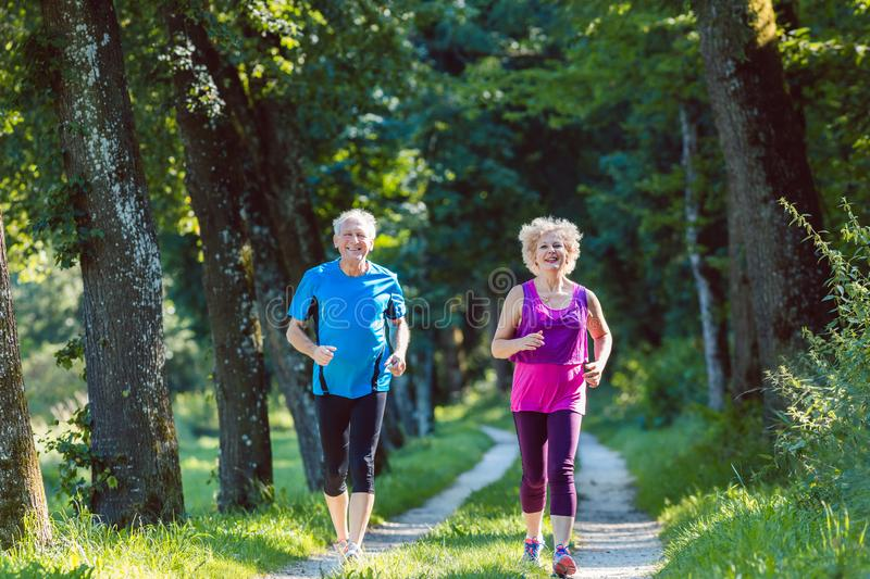 Two active seniors with a healthy lifestyle smiling while jogging. Full length front view of two active seniors with a healthy lifestyle smiling while jogging stock photo
