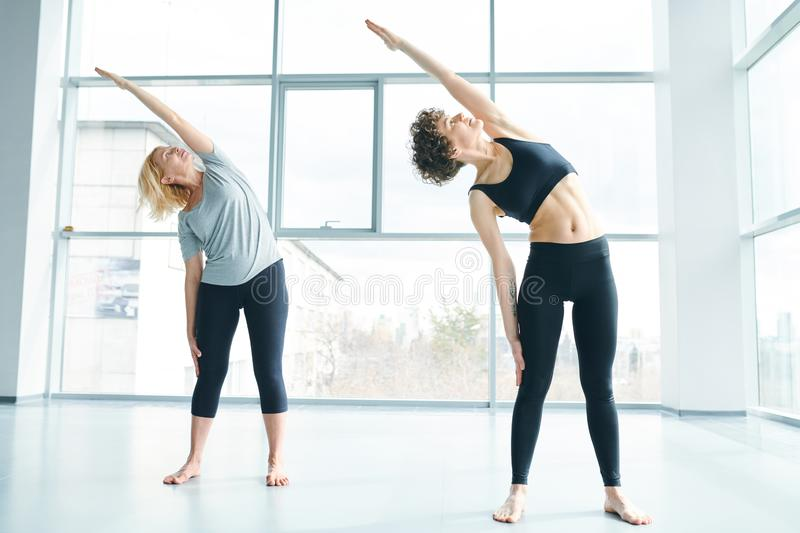 Females exercising. Two active women in sportswear side-bending and looking at heir raised and stretched left arms during workout in gym stock photos