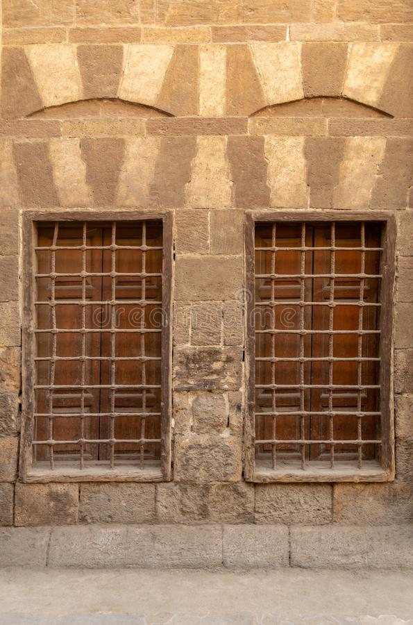 Two adjacent wooden closed windows with iron grid over decorated stone bricks wall, Medieval Cairo, Egypt. Two similar adjacent wooden closed windows with iron stock image