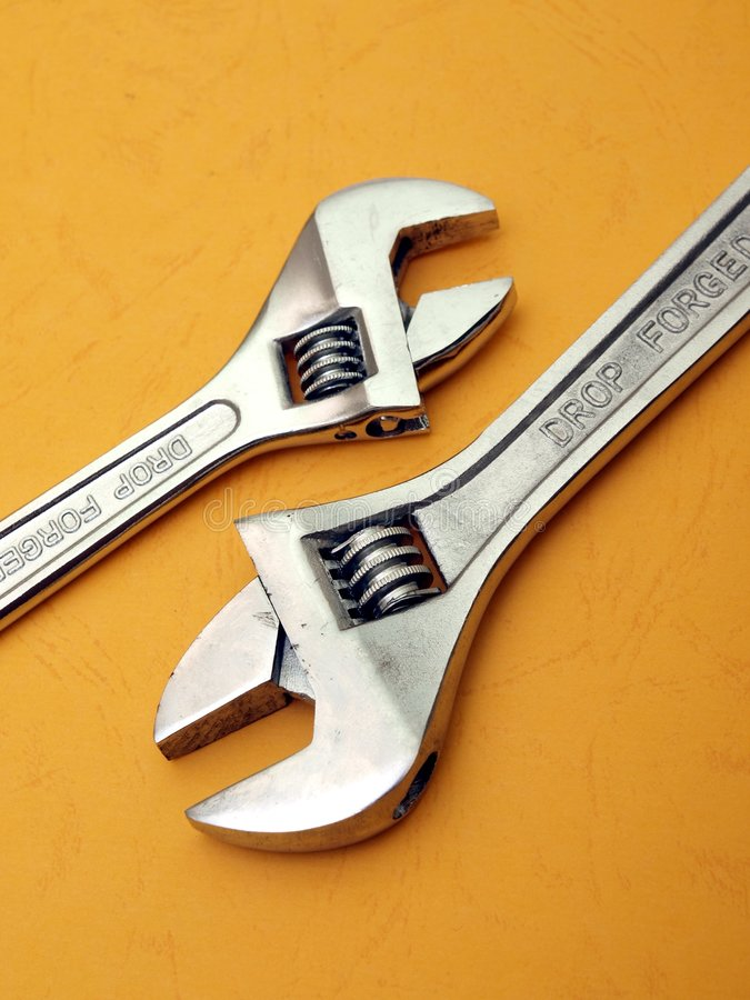 Two adjustable wrench detail on orange royalty free stock photography