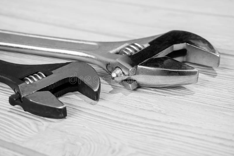 Two adjustable wrenches on the table close up. Two plumbing adjustable wrenches on the light table surface stock photos