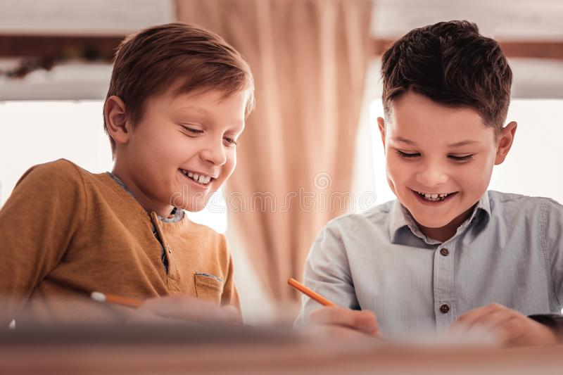 Two adopted children smiling broadly while communicating. Smiling children. Two blonde-haired and dark-haired adopted children smiling broadly while stock photography