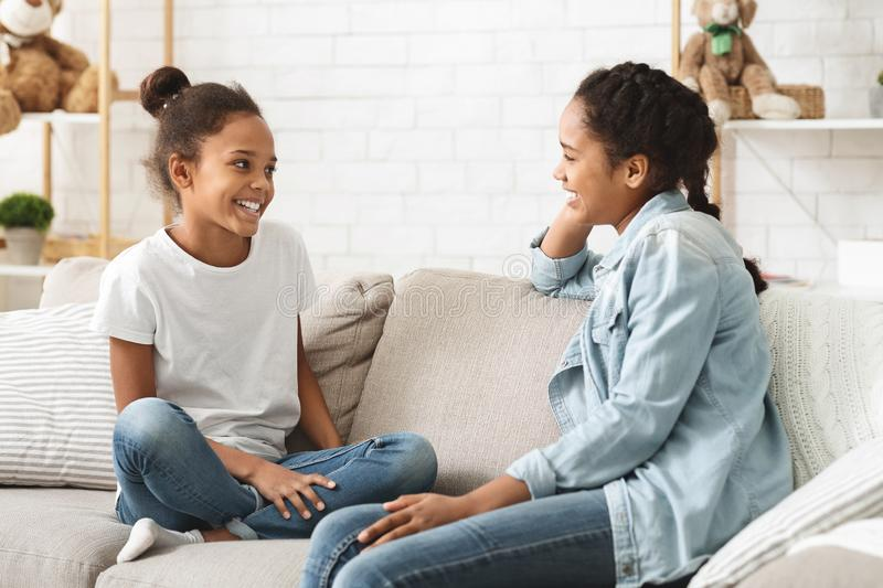 Two adorable girls sitting on sofa at home and talking stock photo