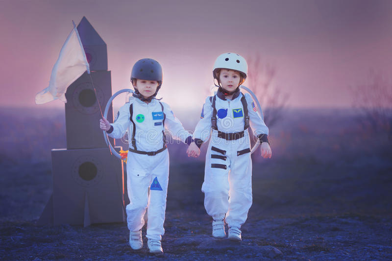 Two adorable children, playing in park on sunset, dressed like a. Two adorable children, boy brothers, playing in park on sunset, dressed like astronauts stock photos