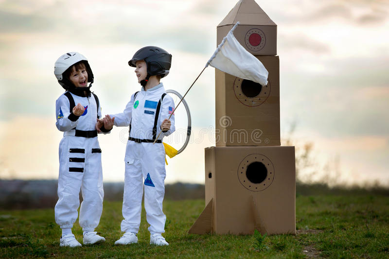 Two adorable children, playing in park on sunset, dressed like a. Two adorable children, boy brothers, playing in park on sunset, dressed like astronauts stock images