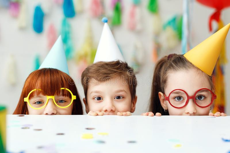 Two adorable girls in eyewear and one boy play game together, celebrate festive event, hide behind table, have cheerful stock images