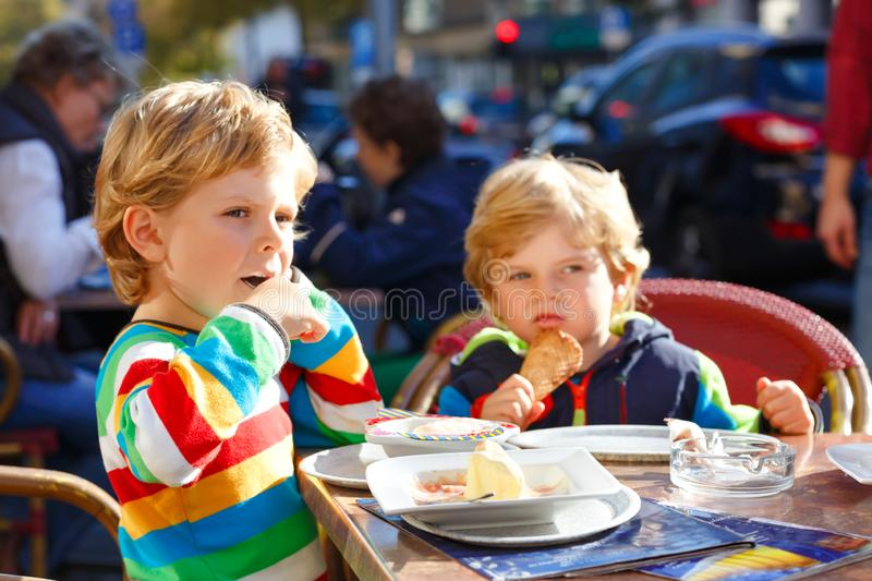 Two adorable kids boys eating ice cream in outdoor cafe. Happy family on sunny day. Healthy children, twins and best royalty free stock photography