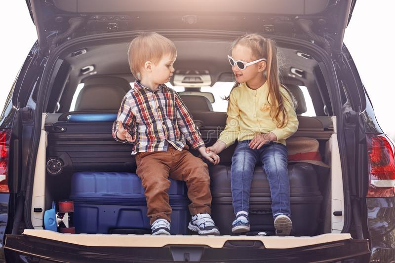 The best education you will ever get is traveling. Little cute kids in the trunk of a car with suitcases. Family road stock photography