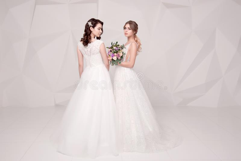 Two adorable ladies wearing in long fashionable dresses holding flowers stock photography