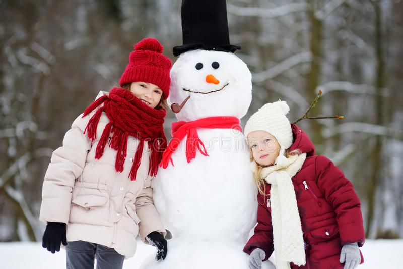 Two adorable little girls building a snowman together in beautiful winter park. Cute sisters playing in a snow. royalty free stock photo