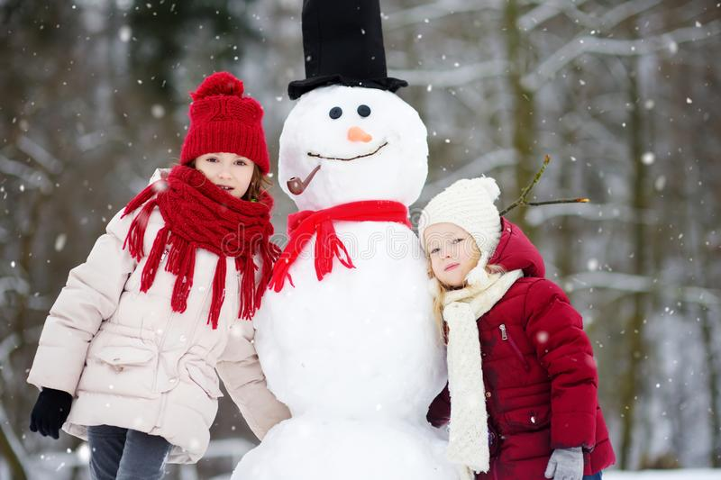 Two adorable little girls building a snowman together in beautiful winter park. Cute sisters playing in a snow. stock image