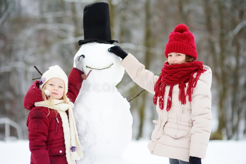 Two adorable little girls building a snowman together in beautiful winter park. Cute sisters playing in a snow. royalty free stock photography