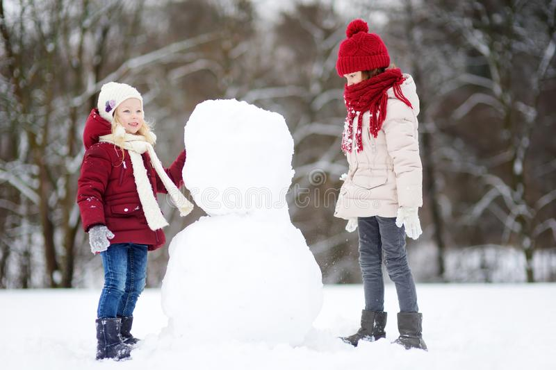 Two adorable little girls building a snowman together in beautiful winter park. Cute sisters playing in a snow. royalty free stock image