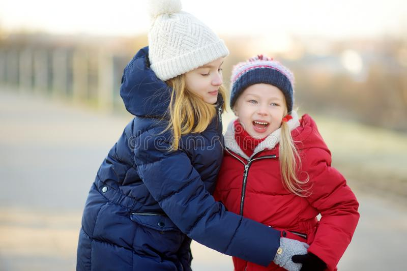 Two adorable little girls having fun together on beautiful winter day. Beautiful sisters playing in a snow. stock photo