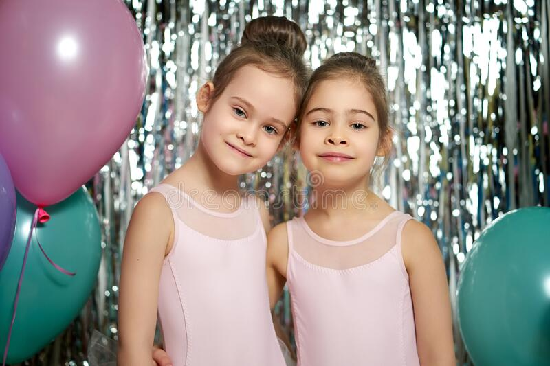 Two adorable little girls are posing on the shiny background royalty free stock photo