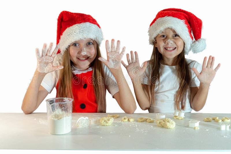 Two adorable little girls in santa claus hats and red christmas apron make cookies with their own hands. Hands raised, noses. Stained with flour. Isolated on a stock photo
