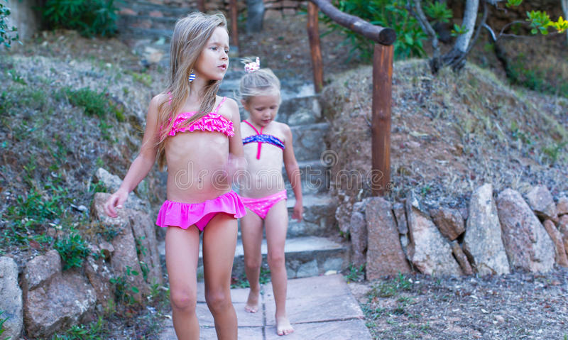 Two adorable little girls in swimsuits during the royalty free stock photography