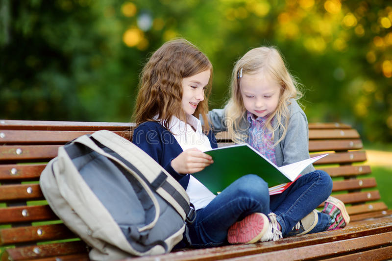 Two adorable little schoolgirls studying in a city park stock photo