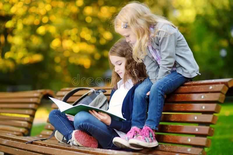 Two adorable little schoolgirls studying in a city park stock image