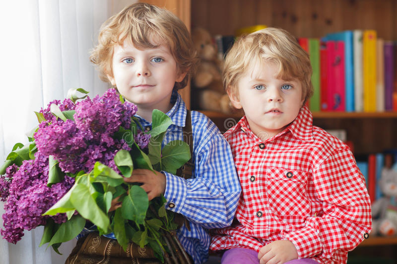 Two adorable little sibling boys with blooming lilac flowers stock photography