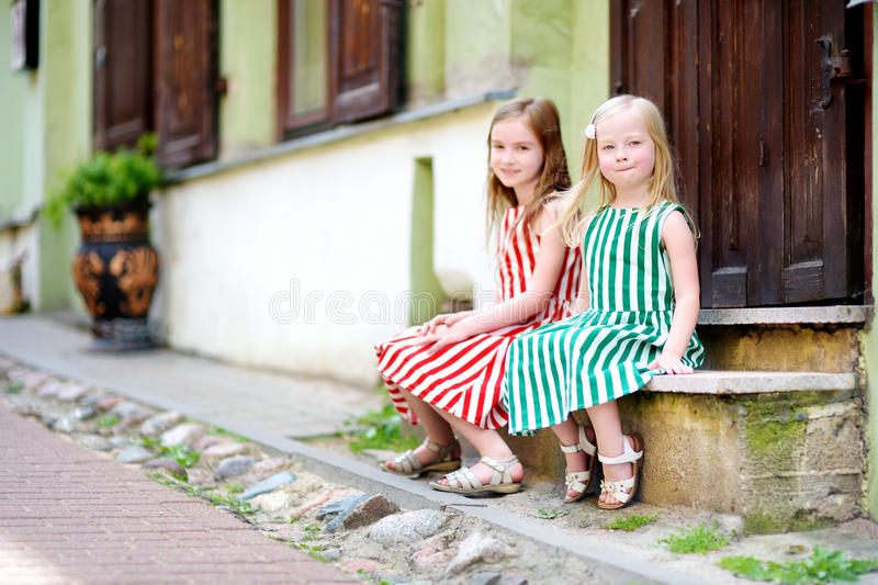 Two adorable little sisters having fun on famous Literatu street in Vilnius stock image