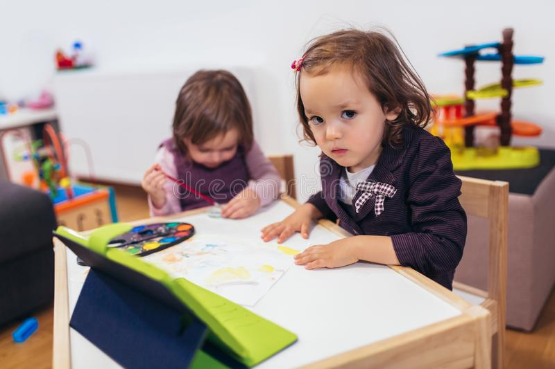 Adorable little sisters playing with a digital tablet at home royalty free stock photos