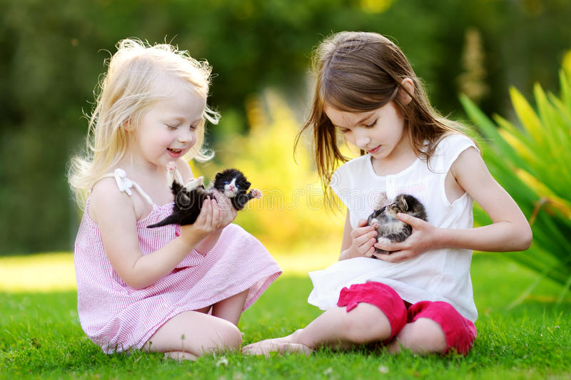 Two adorable little sisters playing with small newborn kittens royalty free stock images