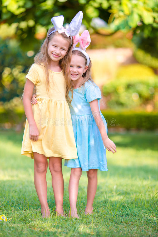Two adorable little sisters wearing bunny ears on Easter day outdoors. Two adorable little sisters wearing bunny ears on Easter day royalty free stock photo