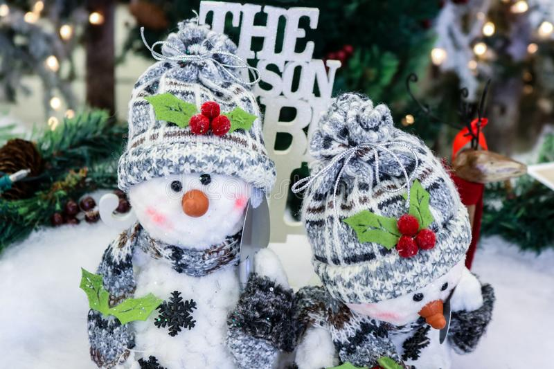 Two adorable ornamental snowmen with snow shovels caps and scarves in front of blurred Christmas background.  royalty free stock images