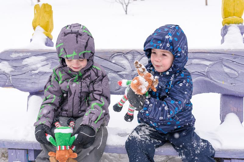 Two adorable preschool kids brother boys in winter wear sit amoung snow and play with toy reindeer.  royalty free stock photos