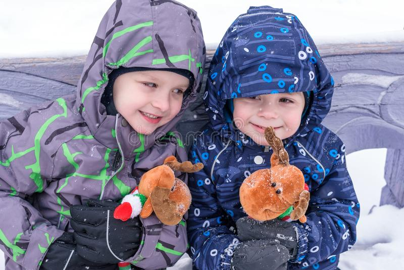 Two adorable preschool kids brother boys in winter wear sit amoung snow and play with toy reindeer.  stock photos