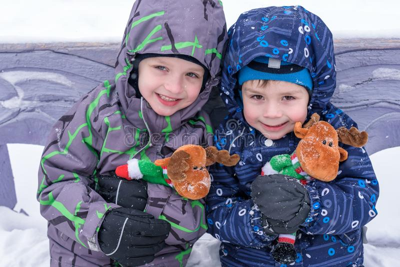 Two adorable preschool kids brother boys in winter wear sit amoung snow and play with toy reindeer.  stock image