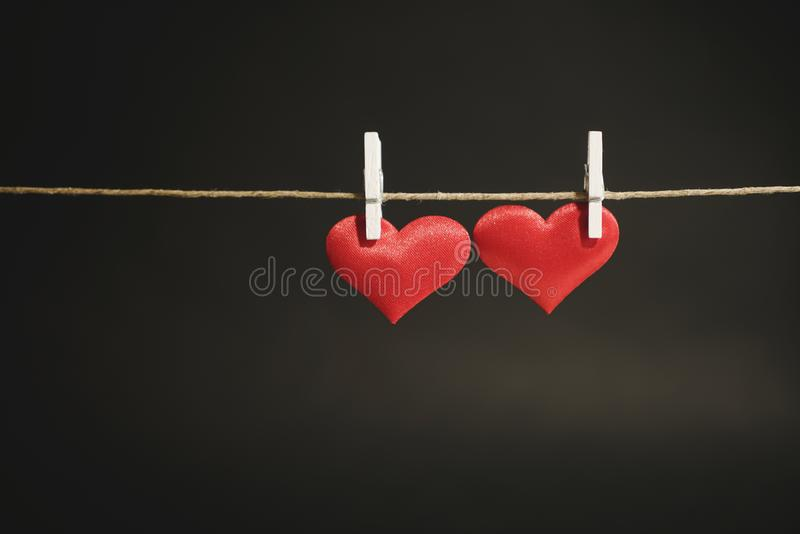 Two adorable red hearts hanging from a string by white clothes peg. Valentine`s Day or romantic occasion with copy space royalty free stock photography
