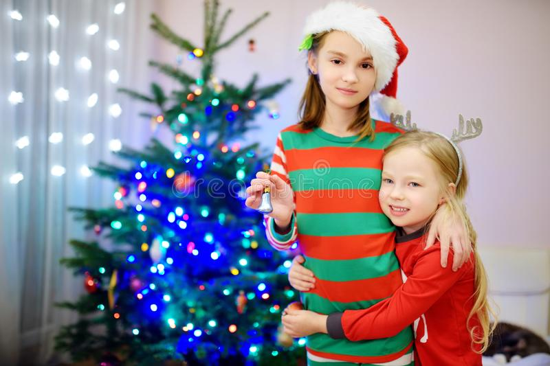 Two adorable sisters decorating a Christmas tree with colorful glass baubles at home. Family leisure at Xmas time. Trimming a fest. Two adorable sisters royalty free stock photos