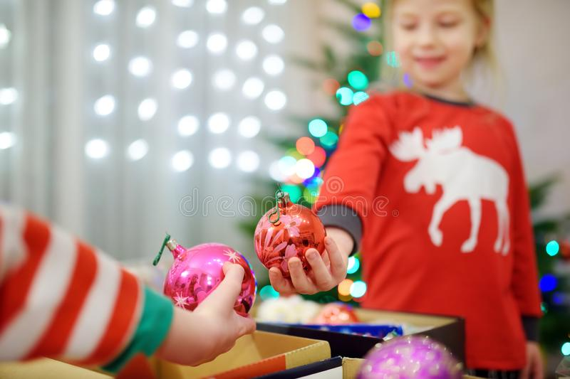 Two adorable sisters decorating a Christmas tree with colorful glass baubles at home. Family leisure at Xmas time. Trimming a fest. Two adorable sisters royalty free stock photo