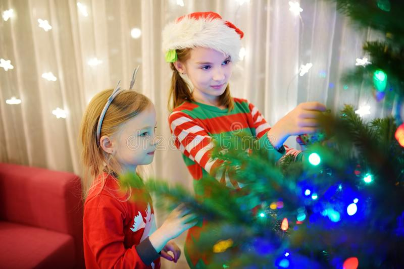 Two adorable sisters decorating a Christmas tree with colorful glass baubles at home. Family leisure at Xmas time. Trimming a fest. Two adorable sisters stock image