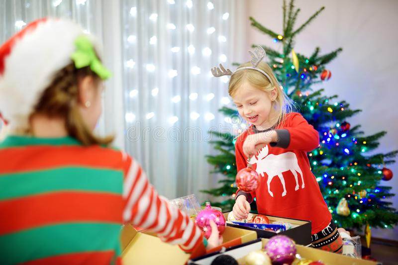 Two adorable sisters decorating a Christmas tree with colorful glass baubles at home. Family leisure at Xmas time. Trimming a fest. Two adorable sisters royalty free stock images